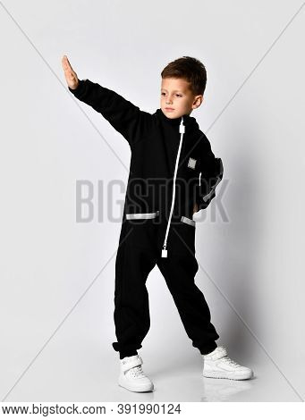 Handsome Boy In Black Warm Jumpsuit Standing With Raised Hand Palm Over Studio Copy Space Looking As