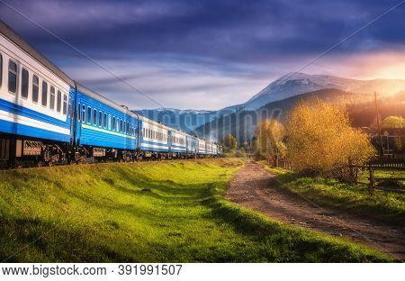 Moving Train In Mountains At Sunset In Autumn. Industrial Landscape With Passenger Speed Train On Ra