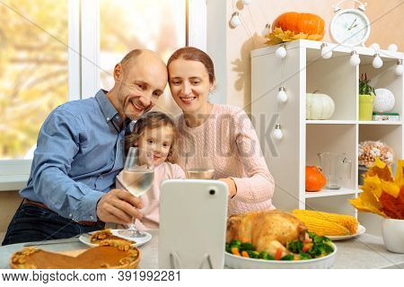 A Happy Family Is Having A Thanksgiving Dinner, Holding A Glass Of Wine And Saying Cheers To Their P