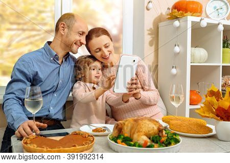 A Happy Family Have A Thanksgiving Dinner And Sends A Video Greeting To Their Parents On A Video Con