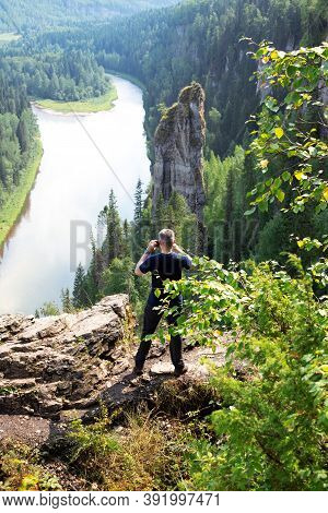 Caucasian Man Stands With His Back Turned And Making Photo Of Beautiful Landscape Of Devils Finger O