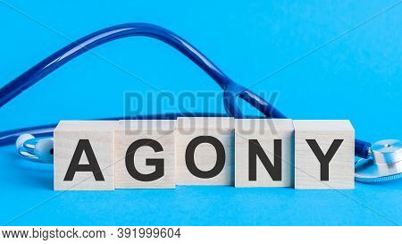 Agony Word Written On Wooden Blocks And Stethoscope On Light Blue Background