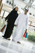 Couple walking in mall holding hands and smiling (selective focus) poster