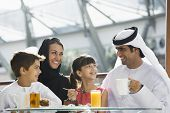 Family at restaurant eating dessert and smiling (selective focus) poster