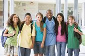 Six students standing outside school together smiling poster