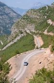 car is traveling uphill the winding dirt road between the albanian mountains down into the Kelmend Valley poster