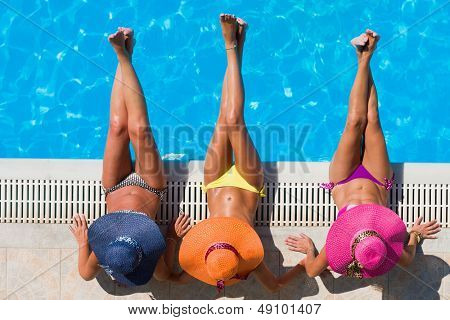 Three women in bikini wearing a straw hat by the swimming pool