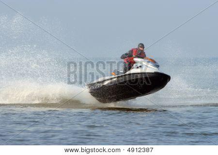 Jet Ski in Aktion mit Wasserstrahl auf das blaue Meer