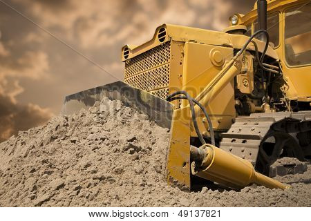 Bulldozer at work on the orange sky background