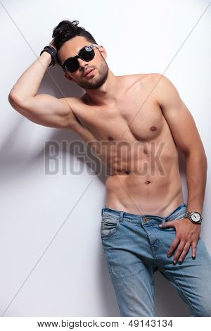 young topless man with sunglasses posing with a hand at his head and a thumb in his jeans loop. on light gray background
