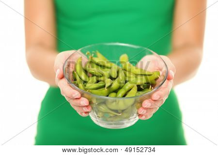 Soy beans - healthy food. Woman showing healthy green fresh edamame bean.soya beans in close up isolated on white background in studio.