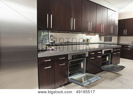 Interior of empty commercial kitchen with open oven and cabinets