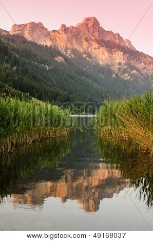 Mountain With Afterglow And Reflection In The Water Of A Lake