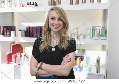 Portrait of happy hairdresser standing arms crossed against shelves at salon