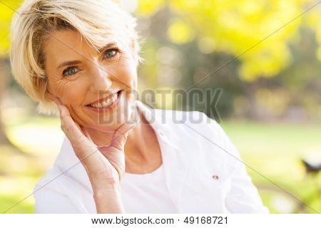 Porträt des schönen middle aged Woman sitzen im Park