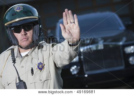 Confident middle aged traffic cop signaling stop gesture with car in background