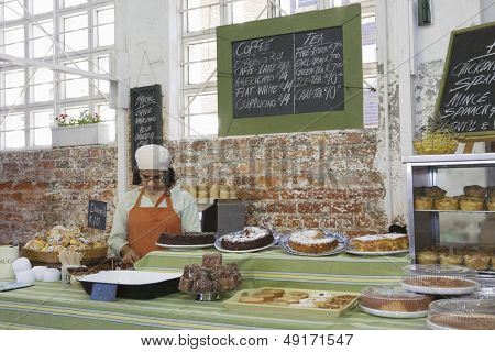 Middle aged female owner working at cake shop