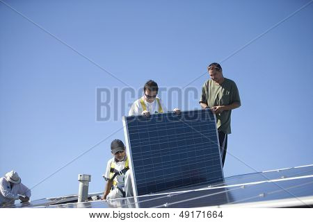 Group of multiethnic workers working on solar panel against clear blue sky