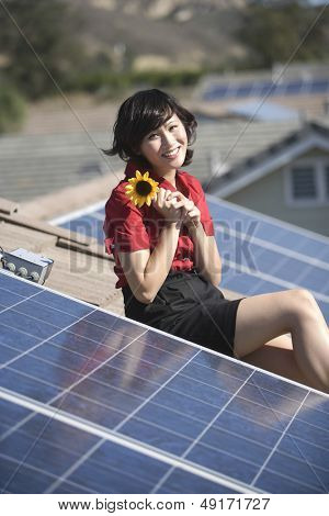 Beautiful young woman holding sunflower while sitting by solar panel on rooftop