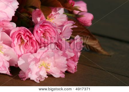 Cherry Blossoms On A Wooden Table