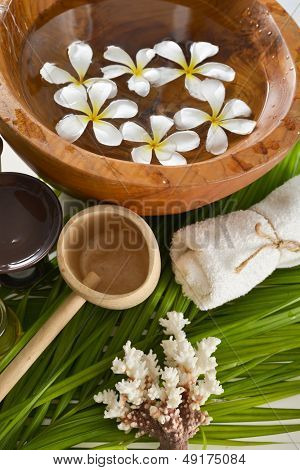 White frangipani in wooden bowl of with spoon,towel ,shell and green leaves