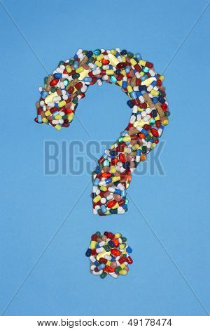 Various pills forming question mark on blue background
