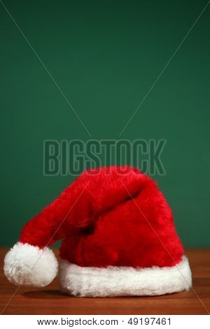 Santa Clause Red Hat With Copy Space on Green and Wood Background