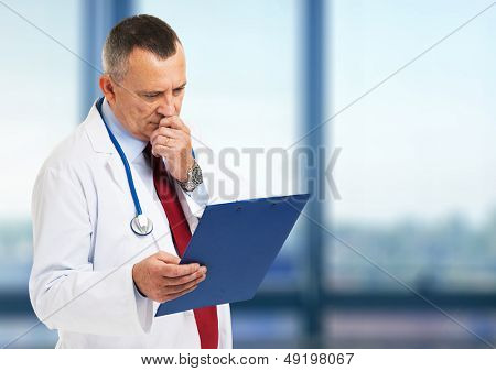Senior doctor reading a case history poster