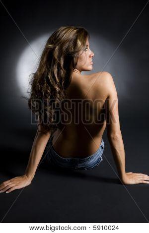 Dramatic Studio Shot Of Topless Brunette In Jean Shorts