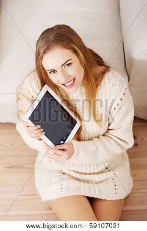 Beautiful caucasain woman holding tablet and sitting on the wooden floor.