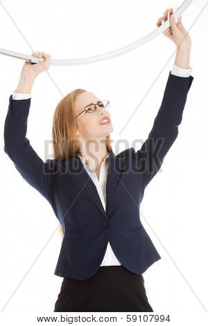Beautiful business woman holding sth heavy above her. Isolated on white.