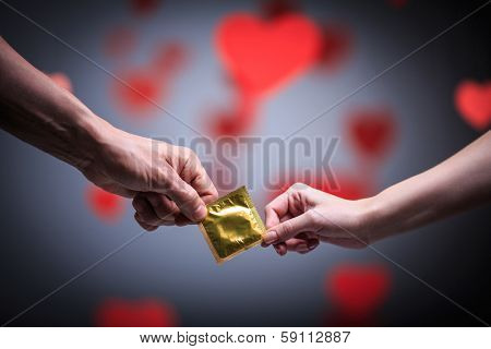 Two hands holding a condom