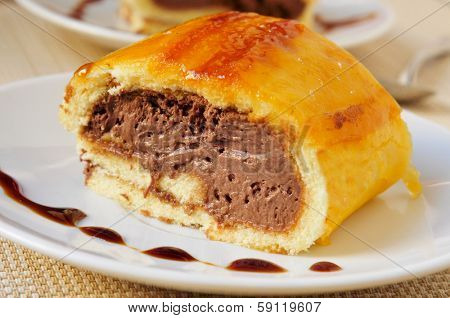 a piece of brazo de gitano, typical spanish swiss roll, filled with chocolate