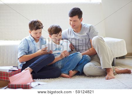 Portrait of cute boys and their father looking through pictures at home
