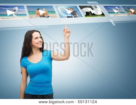 advertisement concept - attractive teenager in casual clothes pointing her finger at videos