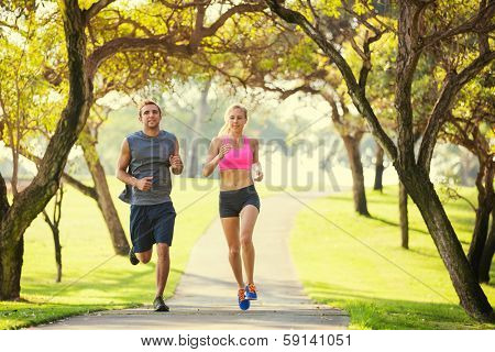 Couple jogging running outside in the park at sunrise on beautiful path. Healthy lifestyle fitness concept.