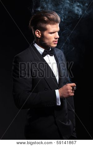 side of a fashion man in tuxedo smoking a cigar on dark studio background