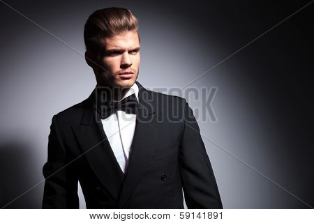 attractive young man wearing elegant black suit and bow tie on gray background
