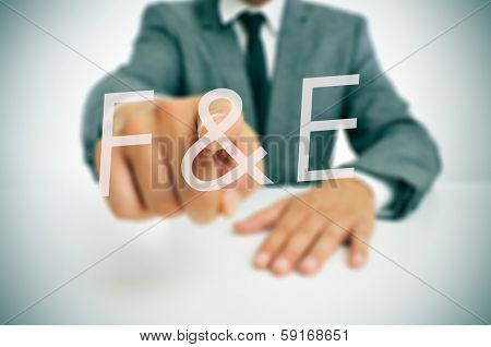 businessman wearing a suit pointing to the term F and E, forschung und entwicklung, research and development in german, written in the foreground