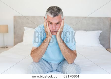 Portrait of sad senior man with head in hands sitting on bed at home
