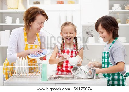 Kids and mother washing dishes - having fun together in the kitchen