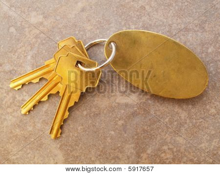 3 Gold Keys And Blank Keychain On Tile