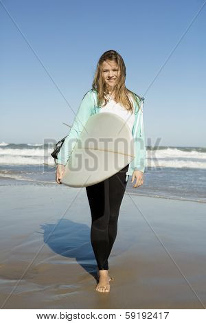 Tenage girl walking in the beach with her surfboard