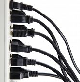 Too many electrical cords connected to a white power strip or extension block. Isolated on white.  poster