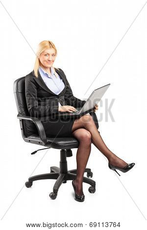 Businesswoman working on laptop seated on chair isolated on white background
