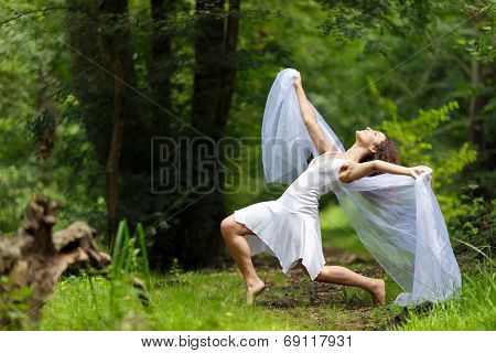 Artistic portrait of a beautiful barefoot woman in a stylish white dress striking a dramatic pose with her outstretched arms draped in filmy white chiffon against a forest backdrop of lush green trees poster