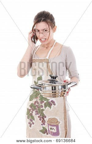 Nervous Housewife In Apron Holding Pot And Talking On Mobile