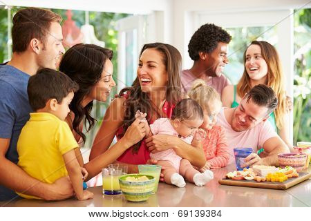 Group Of Families Enjoying Snacks At Home