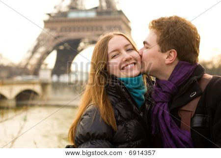 Happy loving couple in Paris kissing by the Eiffel Tower poster
