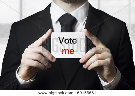 politician holding sign vote me